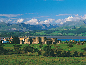 Beaumaris Castle with snowdonia mountains.jpg